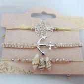 Conjunto de 3 pulseras ajustables de hilo beige con adornos de metal y caracolas.