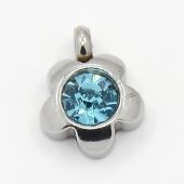 Colgante acero inoxidable flor con cristal facetado azul 9x7x4mm. Agujero 1,5mm